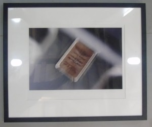 Framed photograph showing an artistically blurred close-up of the 'Handbuilt in England' badge on Aston Martin cars