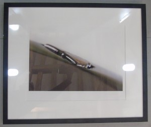 Framed photograph showing a close up of an enamel Aston Martin 'wings' badge