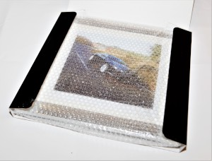 Framed presentation image of an Aston Martin DB9 from the Millbrook Performance Driving Course, in a box