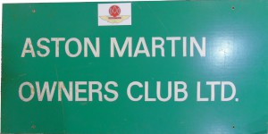Large green painted sign for the Aston Martin Owners Club Ltd